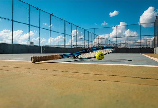 Raquete e bola de tênis na área de lazer