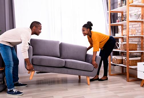 Casal mudando sofá de lugar